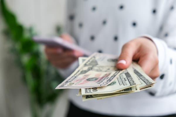 Жінка тримає готівкові гроші.